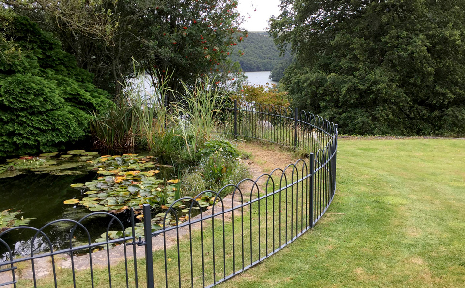 Traditional metal fencing around a pond